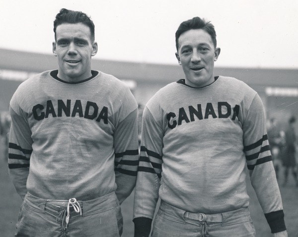 two men in football uniform with CANADA across front