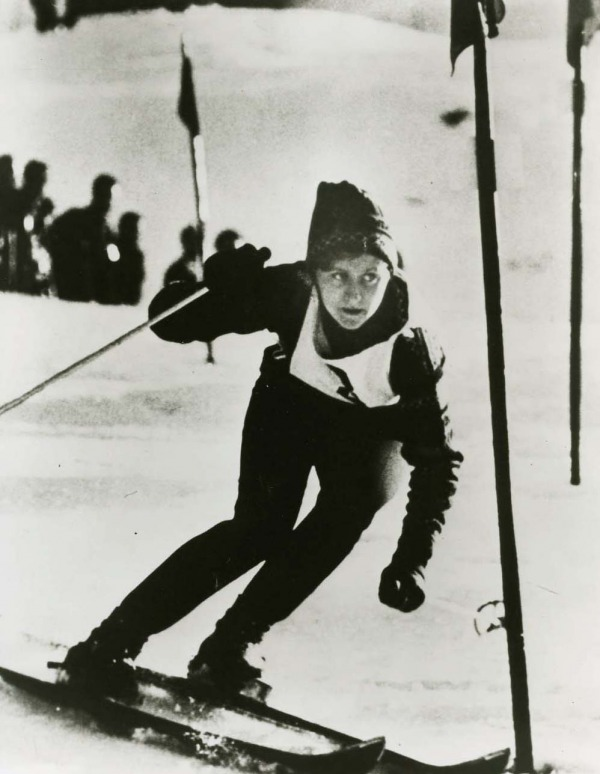 photograph of Anne Heggtveit skiing wearing bib #3 and sunglasses
