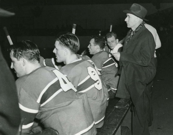 Photograph of Dick Irvin behind hockey bench with players