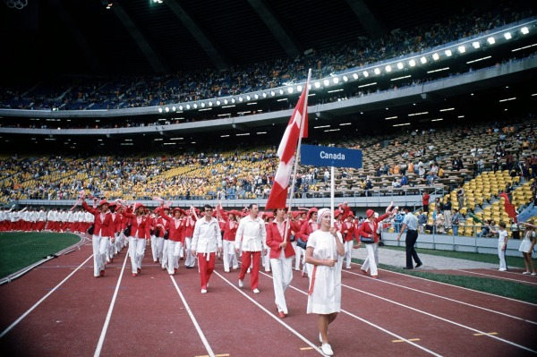 Team Canada in red and white outfits marching behind flag and sign
