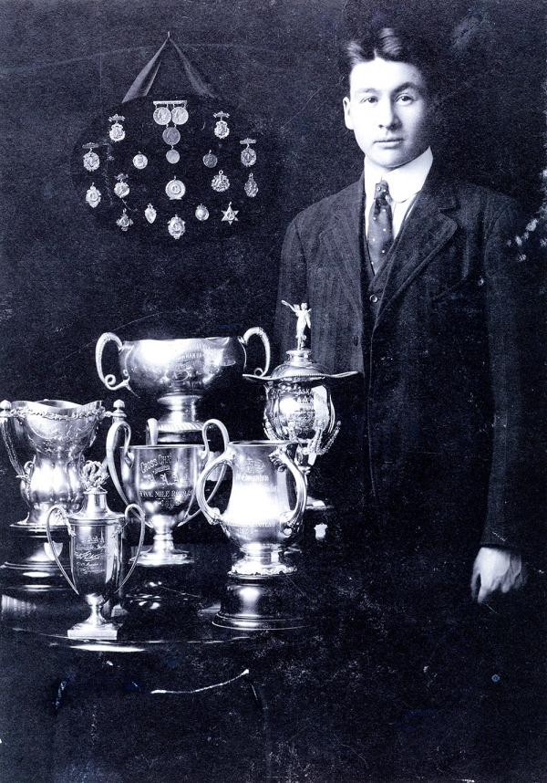 Photograph of Alex Decoteau with trophies and medals