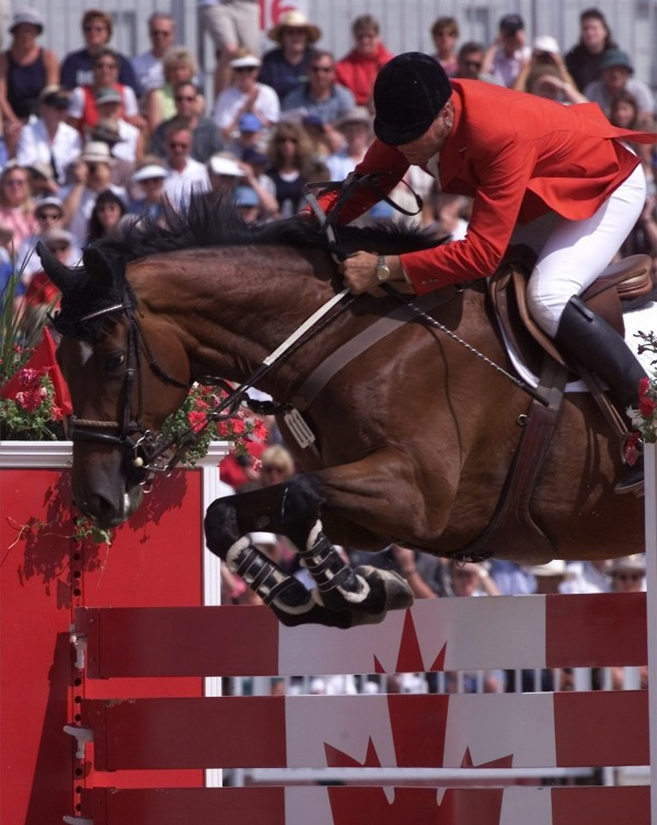 Ian Millar jumping his horse over Canada jump