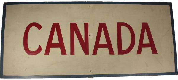 Rectangular wood sign which reads CANADA