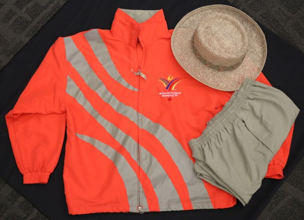 volunteer orange and grey jacket with Games logo and straw hat