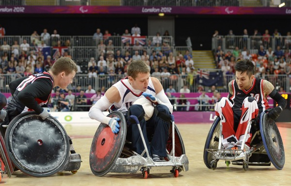 photograph of three players competing in wheelchair rugby
