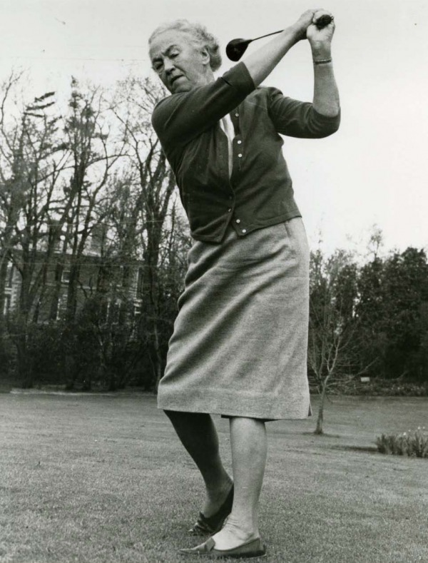 photograph of an older Ada Mackenzie swinging golf club