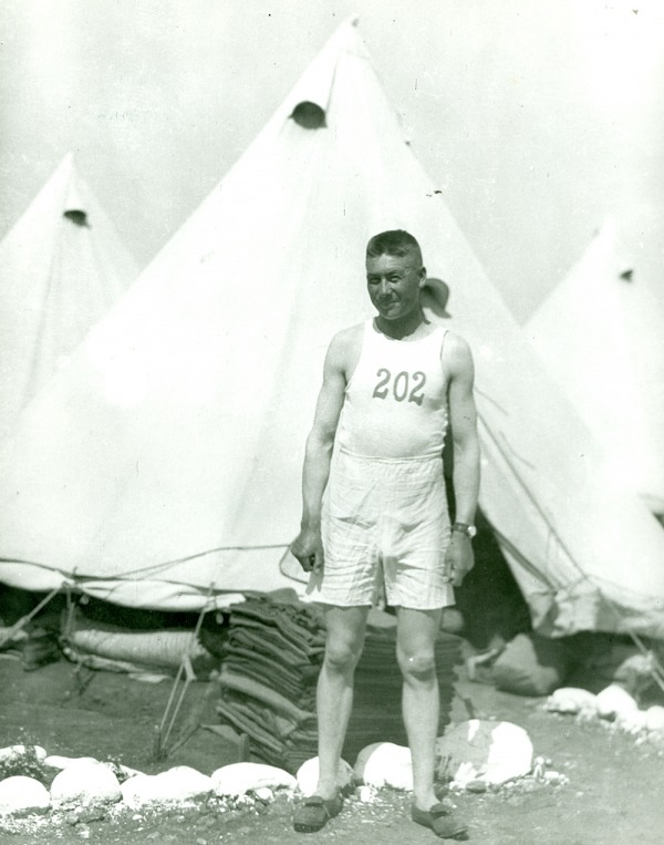 Photograph of Alex Decoteau standing in front of tent