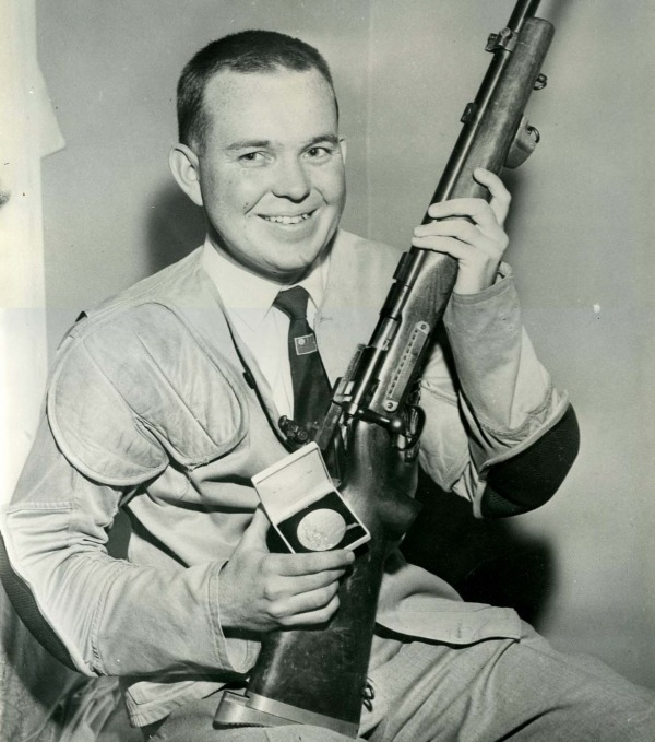 Photograph of Gerry Ouellette holding a rifle and medal