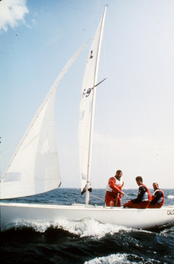 photograph of three men sailing in boat