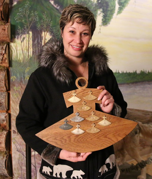 Meika McDonald holding wooden ulu shaped board with her ulu's mounted on the board