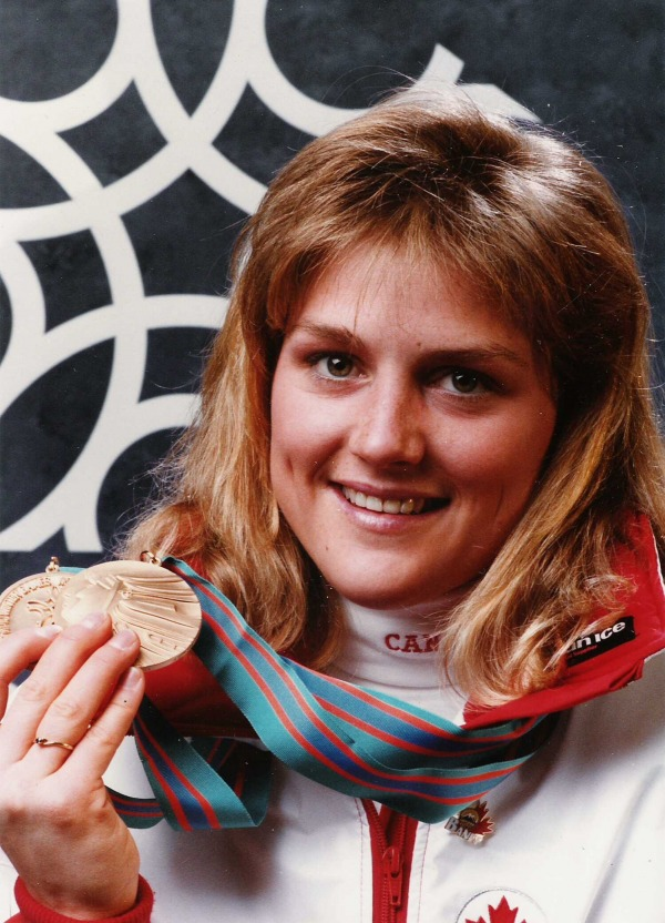 photograph of  Karen Percy holding two Olympic bronze medals