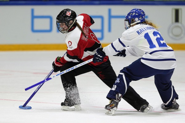 Photograph of two ringette players with sticks and plastic ring