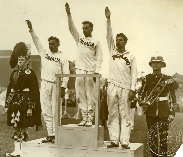 Photograph of three athletes standing on podium, Percy Williams in centre
