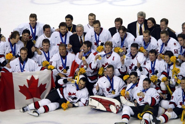 photograph of Team Canada with gold medals at centre ice