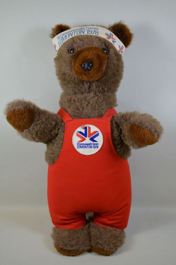 Toy bear wearing red overall with Commonwealth Games logo