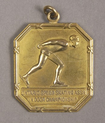 octagonal gold medal with image of speed skater