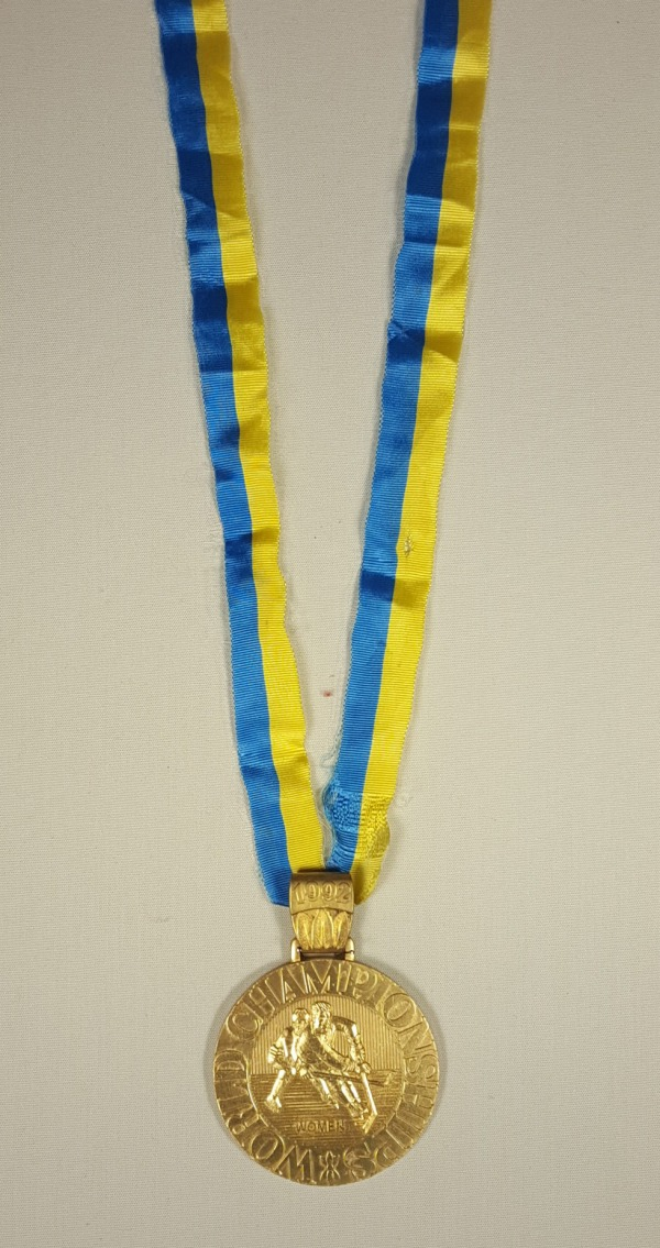 gold medal on yellow and blue ribbon