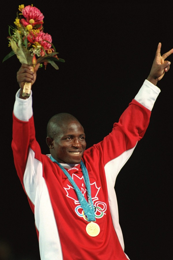 photograph of Daniel Igali with gold medal and flowers