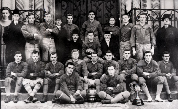 Photograph men in football uniform with two trophies