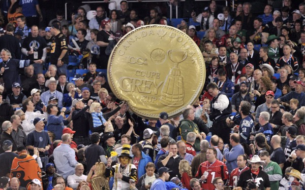 fans hold homemade copy of the Grey Cup Loonie