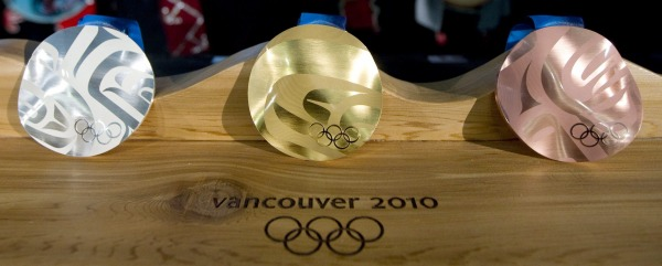 three Olympic medals on wood base
