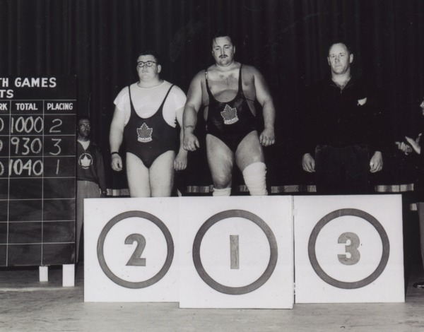 Photograph of winners standing behind podium, Doug Hepburn at centre