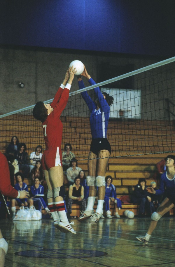 Photograph of two players jumping at a volleyball net