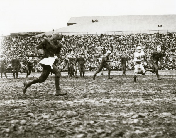 photograph of a player running with football through muddy field
