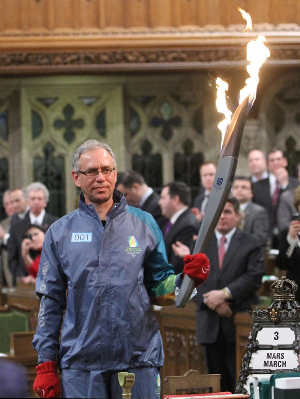 Photograph of Arnold Boldt holding 2010 Vancouver Games torch