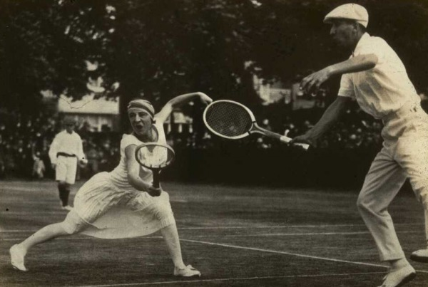 woman in white tennis dress playing mixed doubles game