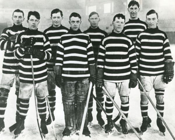 photograph of team wearing black and white striped jerseys