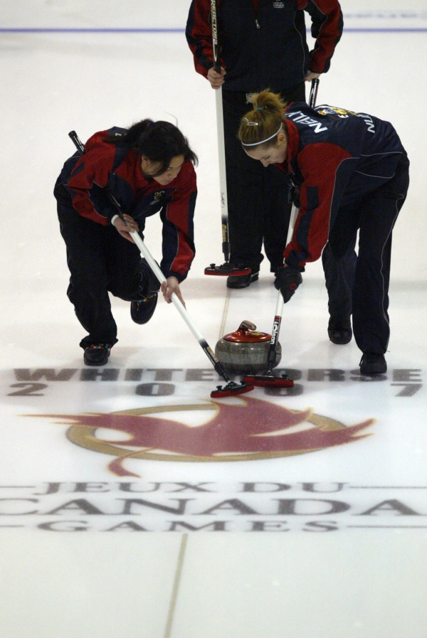 Photograph of curlers with Canada Games logo in the ice
