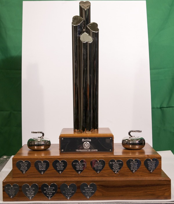 Scotties trophy with four plinths, two curling rocks, and heart shaped engraved silver plaques.