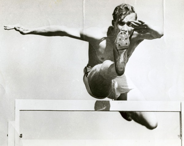 photograph of John Loaring jumping over hurdle