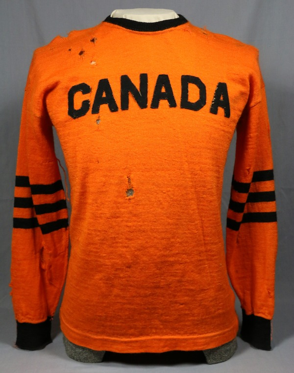 orange football jersey with CANADA in black letters
