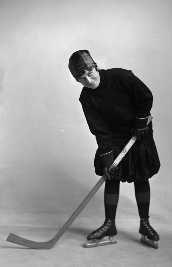 photograph of woman wearing bloomers on ice skates holding hockey stick