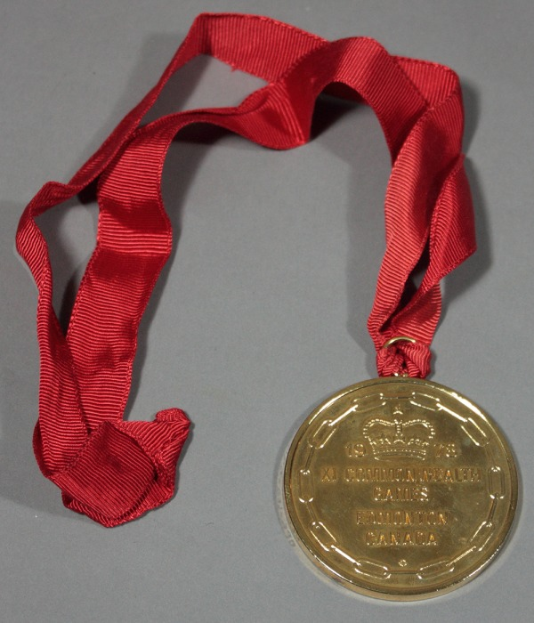 Gold medal with linked chain and crown on red ribbon