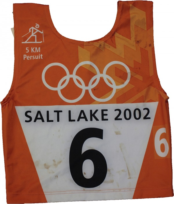 orange race bib with Olympic rings and number 6