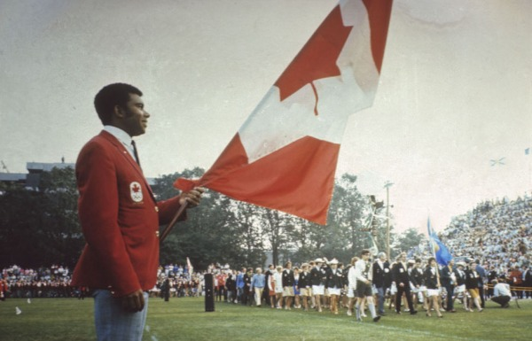 Photograph of Harry Jerome holding Canadian flag
