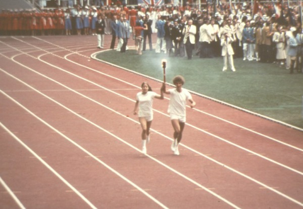 two torchbearers running in the Olympic stadium with torch