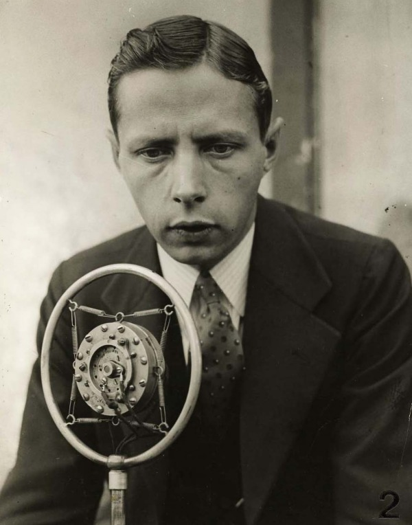 photograph of Foster Hewitt behind microphone