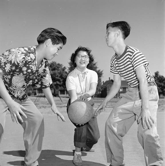 photograph of three children playing basketball