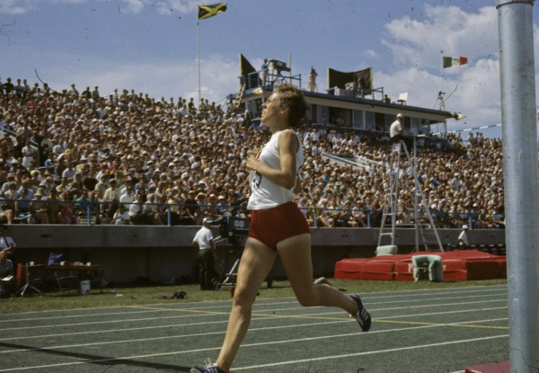 photograph of Abby Hoffman racing with crowd in background