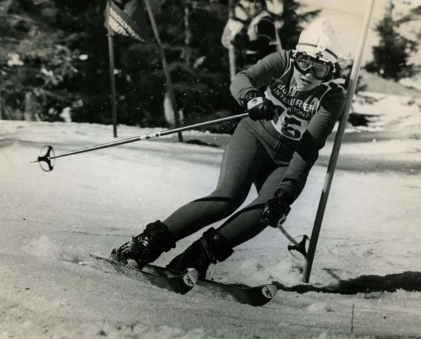 photograph of Betsy Clifford skiing downhill around ski pole