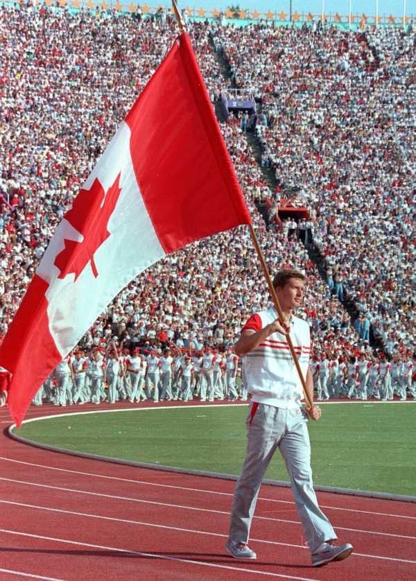 photograph of Alex Baumann carrying Canadian flag