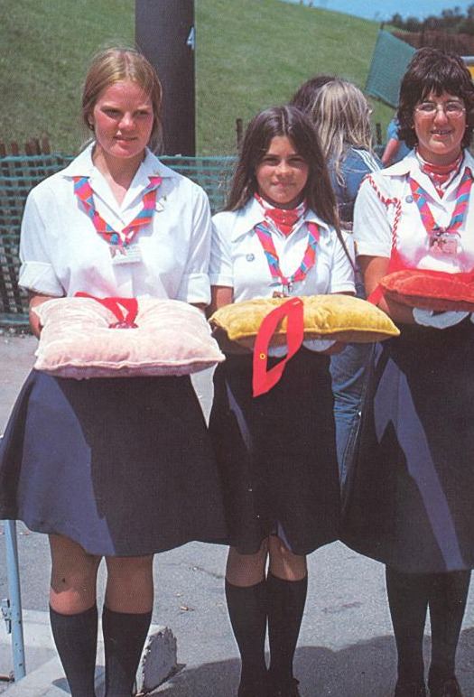 photograph of three girls in uniform holding medals on cushions