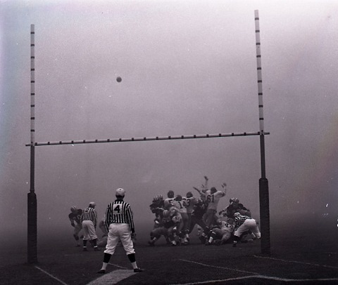 photograph of football above goalposts with players and referee in fog