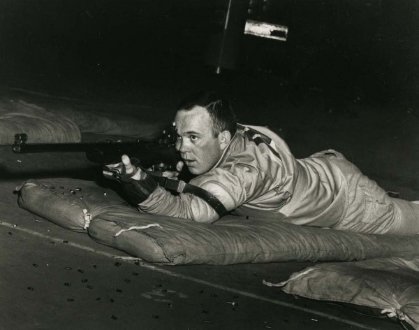 Photograph of Gerry Ouellette lying down on the ground shooting rifle
